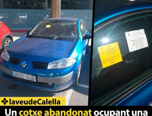 Un cotxe abandonat ocupant una plaça d'aparcament als Codina